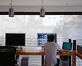 Working at the computer in a modern office with white panel curtains at the window