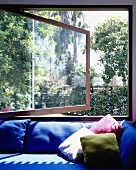 Sofa covered with blue upholstery and colorful pillow in front of an open window with a garden view