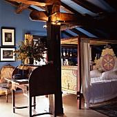 Blau getöntes altes Dachzimmer mit bemaltem Himmelbett und offenem Sekretär