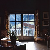 Dark living room with baroque armchairs beside balcony doors and a view of the mountains