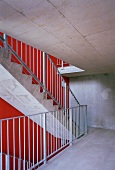 Concrete stairway with red wall and metal banister on the concrete steps