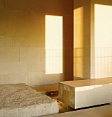 Light and shadows playing on a tiles wall and smooth block of stone next to a roughly hewn one