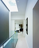 White stairwell with skylight and view into an open passage into the living room of a contemporary home