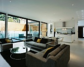 Gray living room suite in an open living room with kitchen in front of a terrace window