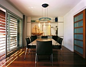 Black leather chair with chrome legs in a dining room in front of terrace doors with wooden blinds