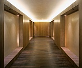 Modern, minimalist lobby with wood built-ins and indirect ceiling lighting