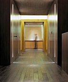 Modern minimalist lobby with built-in wooden closets and integrated strip lighting and view of a man in front of a sideboard