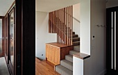 Stairway with built in chest of drawers and transparent wall made of wooden louvers