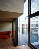 Detail of a concrete living room with brick red leather sofa and a view through the window of the balcony