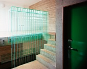 Green lacquered living room door in the concrete stairway and a balustrade made of glass louvers