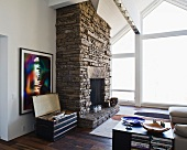 Rustic, natural stone fireplace next to a bank of windows