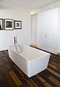A free-standing designer bath tub with floor taps in front of closed sliding doors in a bathroom with rustic parquet flooring