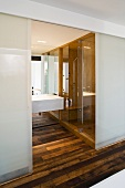 Open sliding door made of opaque glass providing a view of the wash stand in a designer bathroom