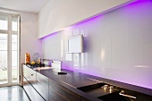 A modern galley kitchen with a glass wall and indirect purple light