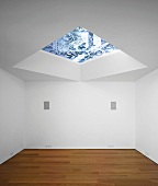 An empty room with a parquet floor and a skylight