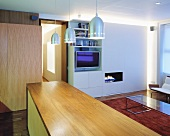 A wooden kitchen counter with a modern, stainless steel pendent lamp in an open-plan living room