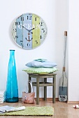 Large wall clock, blue floor vase, chair with pillows and an oar