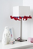 A white table lamp decorated with red feather ribbon and vases decorated with flowers