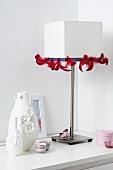 weiße Tischleuchte mit rotem Federband verziert und Vasen mit Blütenapplikation