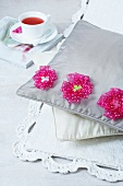 Pillows decorated with flowers on a rub next to a cup of tea
