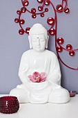A Buddha figure holding an orchid in front of a wall decoration