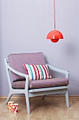 Red hanging lamp above an armchair (50s-60s style)