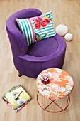 Purple lounge chair with velvet upholstery next to a Moroso table
