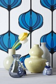 Vases with tulips in front of vintage wallpaper decorated with an onion pattern
