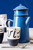 Blue enamel teapot and cup with Dutch writing