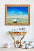 Picture in a gold frame over a rococo wall table and porcelain crockery