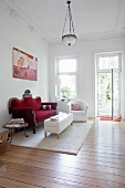 View of a living room with a dark red velvet sofa, white armchair and coffee table