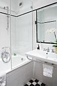 Ein weisses Badezimmer mit Badewanne und schwarz-weissen Bodenfliesen