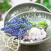 A bunch of grape hyacinths and jewellery in a bowl