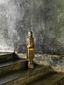 Metal figurine of girl on concrete steps