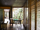 Traditional-style dining area in front of open terrace door and closed wooden blinds on windows