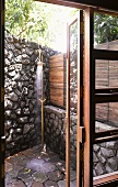 View through terrace door to vintage brass outdoor shower in corner by stone wall