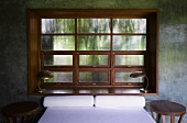 Double bed in front of traditional lattice window in concrete wall