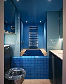 Small, modern bathroom with built-in bathtub and blue mosaic tiles