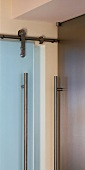Cupboard handle rail next to stainless steel glass door fitting