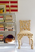 Chair of turned, light root wood next to a chrome bookcase