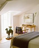 Schlafraum mit schlichter Arbeitsecke und Tisch mit Kamelfigur als Tischgestell vor Fenstertür