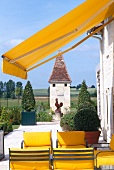 Metal chairs with yellow upholstery under a yellow awning on a terrace