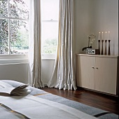 Candles burning in a modern bedroom with a cupboard next to the bay window