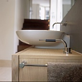 A modern wash basin on a wooden cupboard