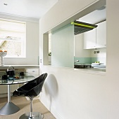 A black plastic, retro-style bucket chair next to a dining table with a large, modern serving hatch with a view into the kitchen