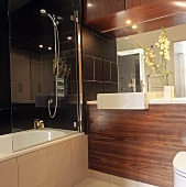 A modern bathroom with wood panelling below the wash stand and a glass shower wall