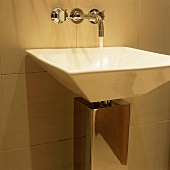 Water running from wall taps into a designer wash basin with chrome cladding around the outlet pipe