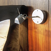 A modern, swivel bedside lamp made of stainless steel and mounted on a wooden panel