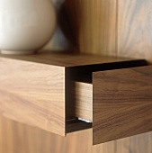 A wood panelled shelf with an open drawer