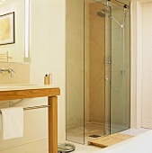 A walk-in shower with a glass door and a wash stand